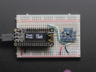 Finger pressing on sensor wired to Feather board, OLED shows increasing pressure.