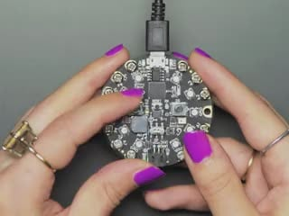Hand pressing buttons on circuit playground, then turning over to show TFT gizmo display an image of a friendly robot or snake