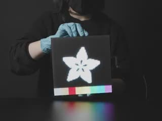 Video of a woman in black slowly rotating a powered-on 64x64 RGB LED Matrix. The matrix displays the Adafruit star flower logo with rainbow sand falling animation.