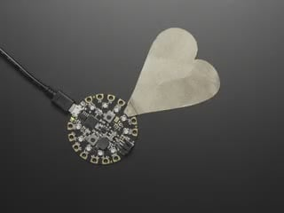 Hand touching heart-shaped cutout of metal connected to circuit board which lights up.