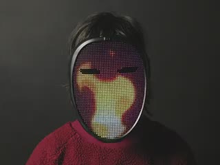 Video of a person wearing LED Matrix Mask. The LED matrix displays a flame animation.