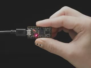 Video of hand holding an ItsyBitsy PCB. An on-board LED glows rainbow colors.