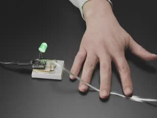 Video of a hand scrunching the ribbon sensor triggering a green LED installed on a breadboard to light up.