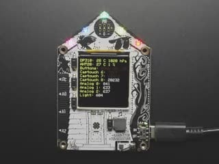 Top-down video of Adafruit Funhouse PCB. The TFT display shows a data readout, and the NeoPixel LEDs glow rainbow colors.