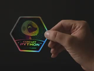 """A hand in motion revealing a holographic sticker with friendly snake wearing a space-helmet. Text says """"Circuit Python Space Explorers"""""""