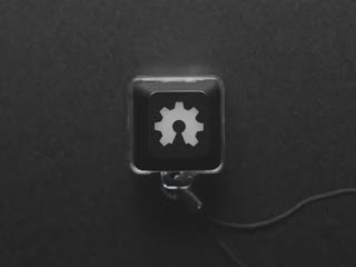 A Black woman's finger presses a keyswitch keychain. A green LED shines beneath an open source hardware logo keycap.
