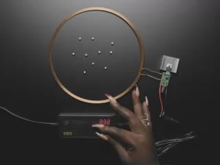 Top view video of a Black hand turning on the adjustable power supply. A wireless charger powers on a pile of bare LEDs.