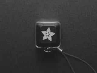 A Black woman's finger presses a keyswitch keychain. A white LED shines beneath an Adafruit logo keycap.