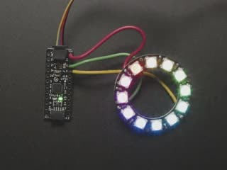 Top view video of a NeoPixel ring soldered with wires to an Adafruit ATtiny817 Breakout. The NeoPixel ring glows rainbow colors.