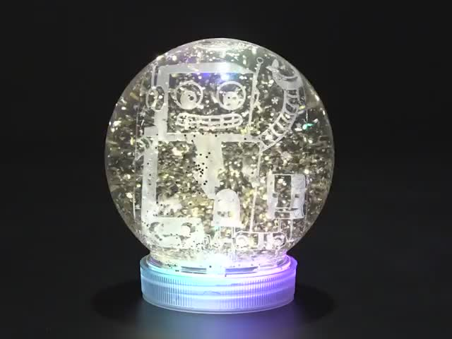 Snow globe with sparkly flakes swirling around, a ring of RGB LEDs in the base animate in a rainbow swirl.