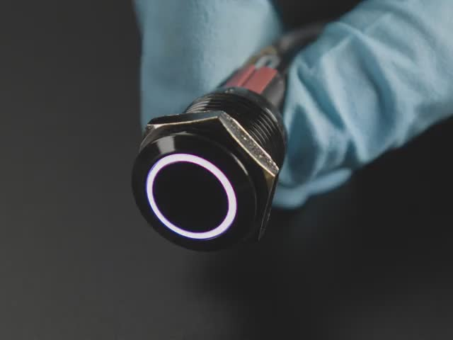 Angled video of 16mm rugged black metal pushbutton with LED ring glowing rainbow colors. A person with gloved hands holds the button and pushes the switch on and off.