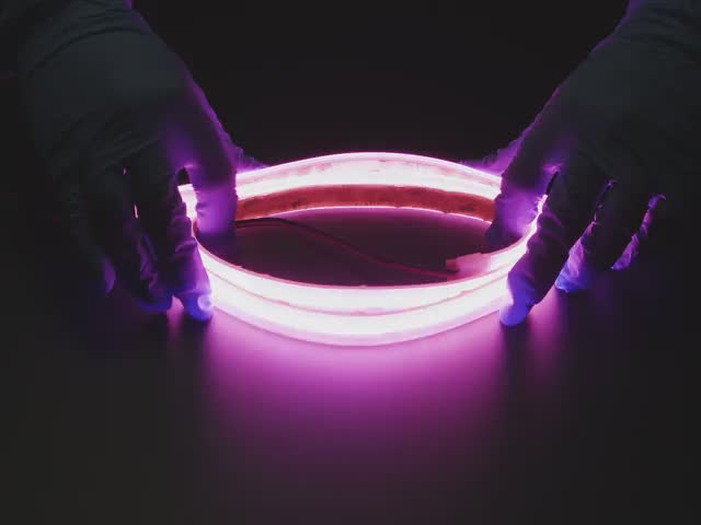 Two hands repeatedly bending and manipulating lit-up flexible pink LED strip