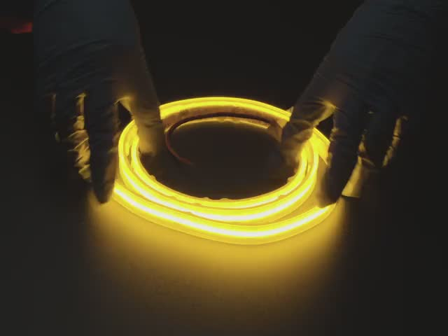 Two hands repeatedly bending and manipulating lit-up flexible yellow LED strip