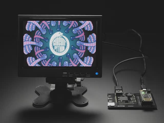 A small monitor and a Gameduino Dazzler PCB with a Feather M4 Express. The monitor displays a swirling kaleidoscopic animation with CircuitPython and Blinka, a friendly coding python.