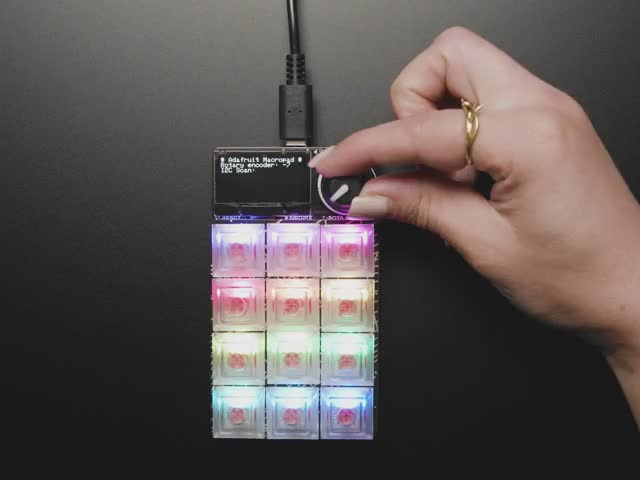 Video of a hand playing with a rainbow-glowing keypad.